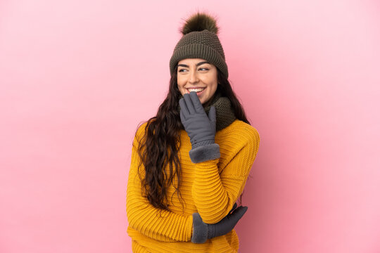 Young caucasian girl with winter hat isolated on purple background looking up while smiling