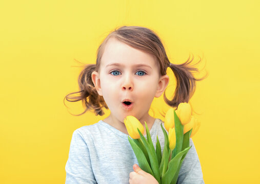 Easter, holidays, spring, mother's and father's day concept - happy, funny,smiling, little child girl in grey dress holds tulips on a yellow background. Happy mothers day. Pantone color of year 2021