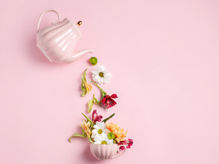 Creative layout with tea pot pouring fresh flowers and leaves into tea cup on pastel pink background. Creative floral spring bloom concept. Still life visual trend. Flat lay.