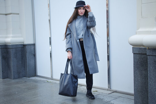 Stylish beautiful girl with long straight hair in a gray coat, black hat, with a black bag walks around the city