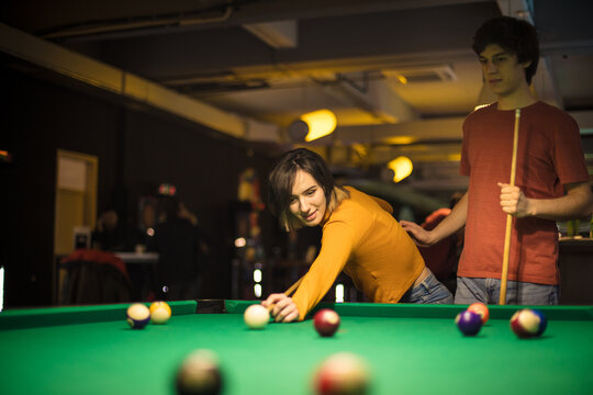 Young couple spending time in billiard room. Billiard game.