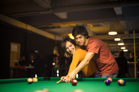 Young couple spending time in billiard room. Boyfriend teaching his girlfriend to playing billiard.