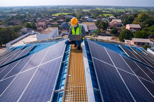 Asian technician checks the maintenance of the solar panels on the roof.
