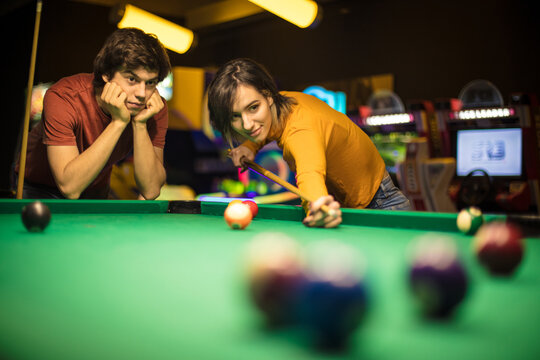 Young couple spending time in billiard room. Woman playing billiard.