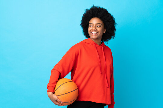 Young African American woman isolated on blue background playing basketball