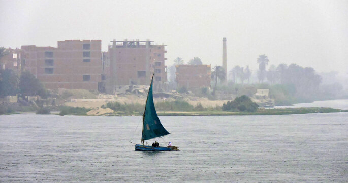 A dhow with a blue sail sailing over the Nile. A dhow is a traditional wooden sailing boat. In the distance is the vague outline of an Egyptian city see-able