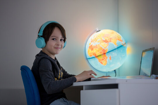 Beautiful child with earphones using laptop while studying at desk at home