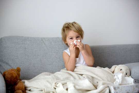 Blond toddler child, wiping his nose in a tissue, sneezing and coughing
