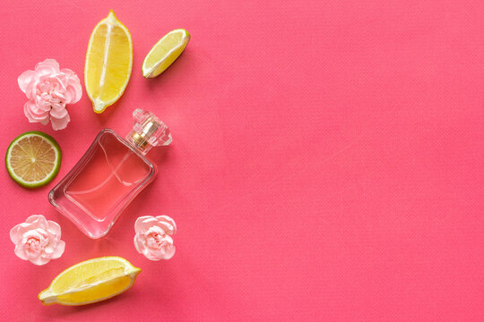 Bottle of perfume with citrus and flowers, top view