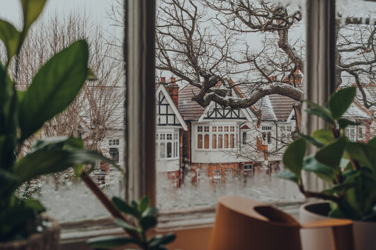 View of the snow through the window from inside the house.