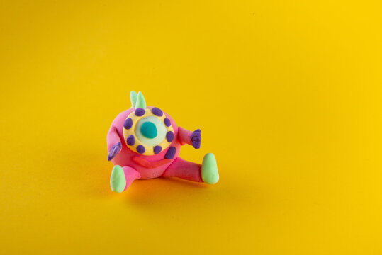 Cute pink round one-eyed fantasy alien sitting on yellow background
