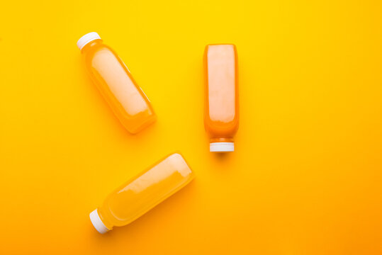 Photo of three bottles with detox juice, orange lemon carrot pineapple.