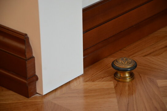 Close-up of a decorative element of the interior of a room - a corner of a white wall, a metal door stopper, wooden baseboards and parquet (laminate)