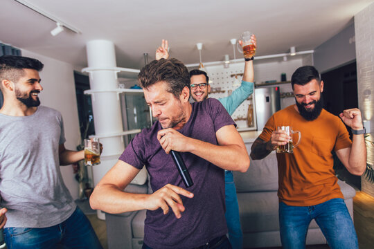 Group of young men spend free time in karaoke, sing and have fun together, with friends, at home.