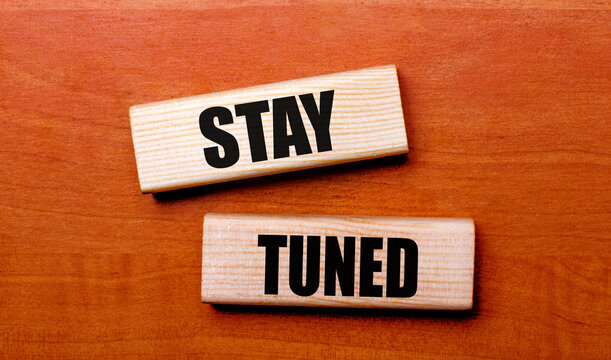 On a wooden table are two wooden blocks with the text STAY TUNED