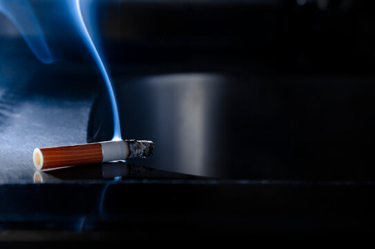 an abandoned cigarette butt with a beautiful plume of smoke. not extinguished cigarette on a dark background