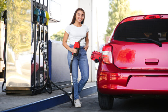 Young woman with fuel pump nozzle near car at self service gas station