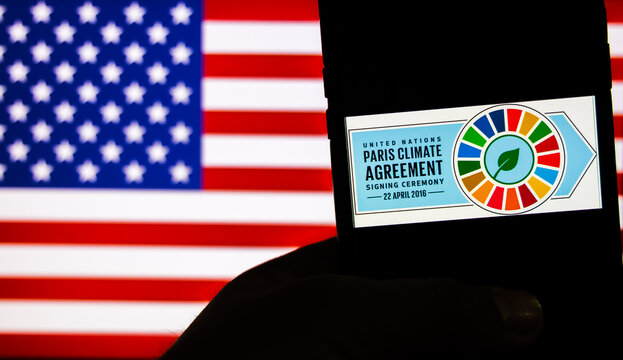 Paris Climate Agreement logo against the flag of United States of America. USA officially re-entered Paris Climate Agreement on 19th Feb 2021 under Biden's Administration.