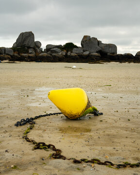 Yellow buoy lying on the beach at low tide