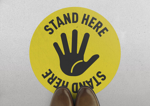 Social distancing concept.  Footprint sign yellow color with text stand here for the print floor.