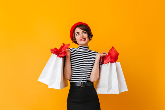 Beautiful girl in stiped t-shirt and red beret holding store bags. Dreamy brunette woman looking up on yellow background.