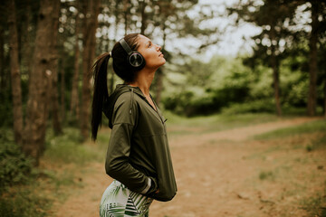 Young beautiful female runner listening to music and taking a break after jogging in a forest