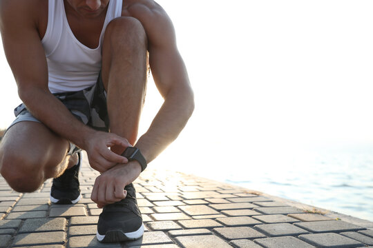 Man checking fitness tracker during training near river, closeup. Space for text