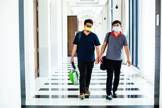 Two young Asian men wearing face masks are walking through the hotel.