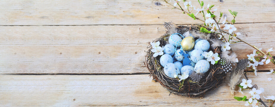 eggs in a basket on wooden table - easter background banner, greeting card