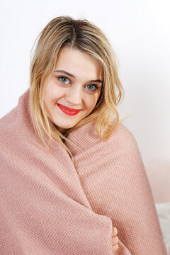 Portrait of a young woman wrapped in a blanket and looking directly at the camera.