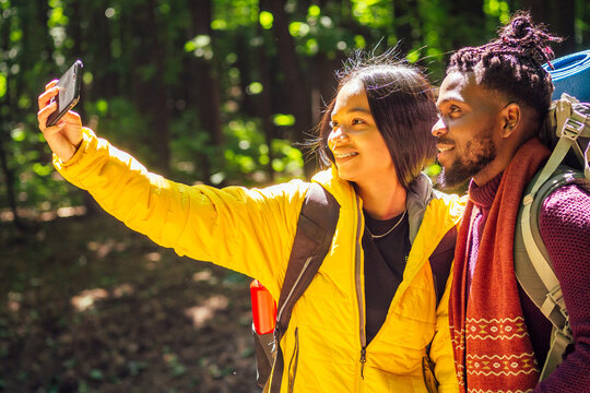 african american mixed race couple in forest making selfie