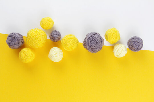 Demonstrating colors of year 2021 - Gray and Yellow.Lots of balls of yarn for knitting or crocheting on a yellow background.The concept of manual labor.Top view.Flatlаy.Copyspace.