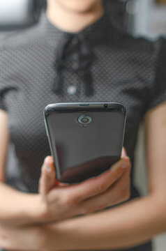 Smartphone in a female hand. A woman holds a mobile phone in her hand.