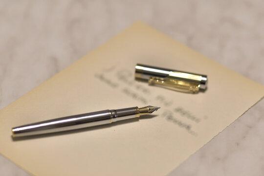 Penna stilografica su tavolo con testo su foglio