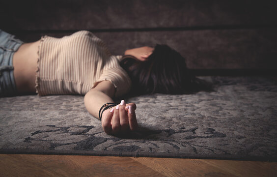 Unconscious young woman lying at home.