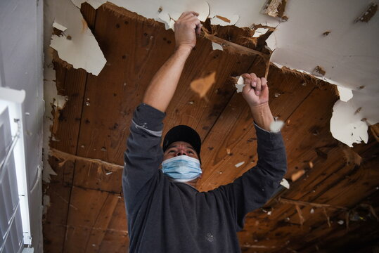 A contractor removes material from a ceiling in a recently-purchased home in Houston