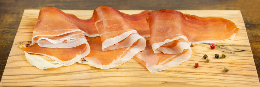 Slices of speck ham on wooden cutting board