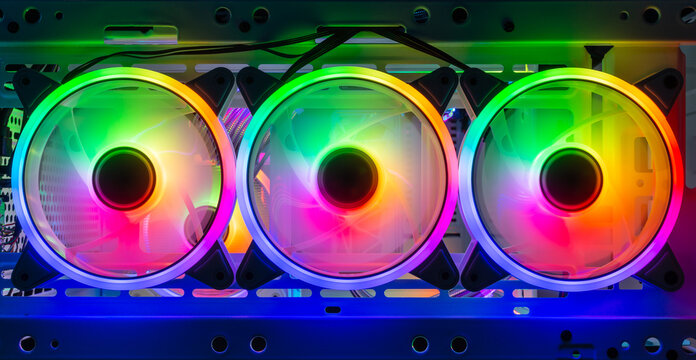 three colorful bright rainbow led rgb pc fan air case cooler white desktop computer chassis. gaming modding water cooling and technology concept background