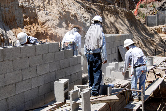 Masonry crew building a block retaining wall