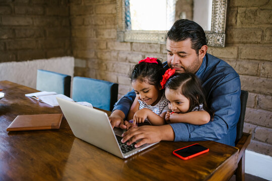mexican father working with computer and his little daughters at home in Mexico City