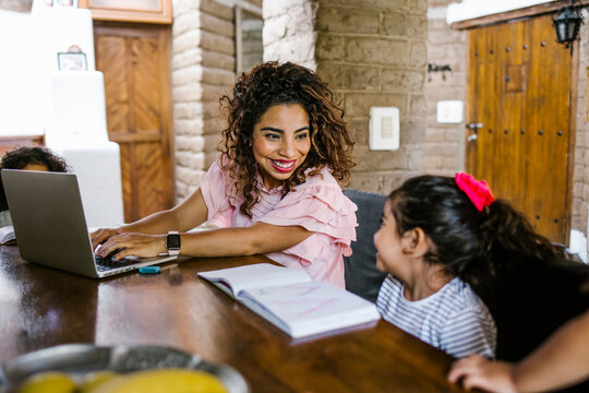 latin mother works on laptop with children playing around, Work from home.
