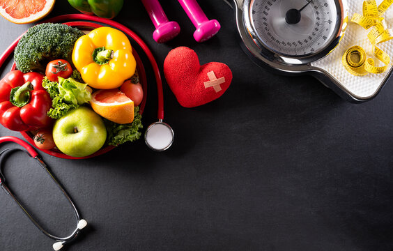 Top view of healthy food in plate with stethoscope, weight scale and red heart for cholesterol diet and diabetes control on dark background. World health day and medical concept.