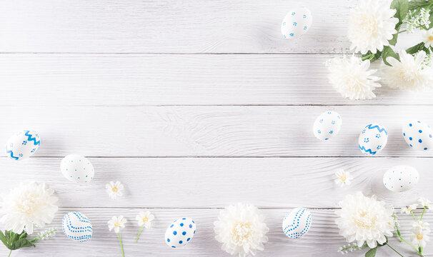 Happy easter! Colourful of Easter eggs in with flower on white wooden background. Greetings and presents for Easter Day celebrate time. Flat lay ,top view.