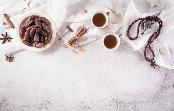 Ramadan food and drinks concept. Ramadan arabian lamp, wood rosary, tea, and dates fruit on dark stone background.