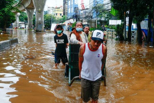 Youths transport an elderly woman in an area affected by floods in Jakarta