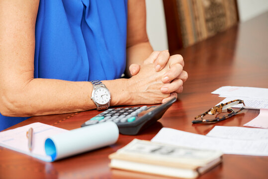 Hands of mature woman sitting at table with utility bills, paychecks and calculator