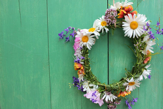 Flower door wreath. Midsummer flower crown on rustic wooden background with copy space. DIY floral wreath. Midsummer night dream decoration
