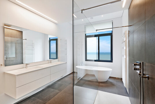 Bathtub in corian, Faucet and shower in tiled bathroom with clear sea through windows