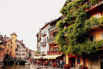 Annecy city water channel, red flowers, old buildings, bridge, green balconies