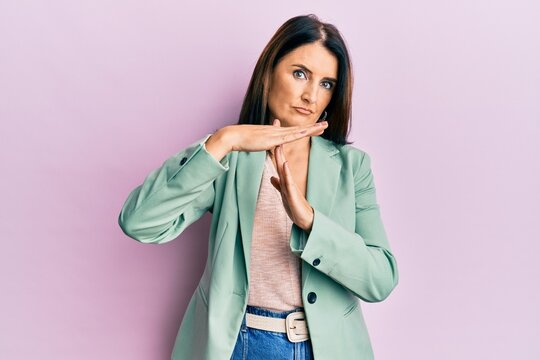 Middle age brunette woman wearing casual clothes doing time out gesture with hands, frustrated and serious face
